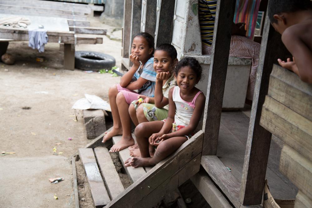 three islander kids sitting on a porch step