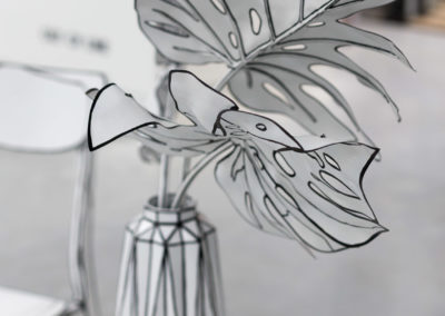 drawing installation of monstera deliciosa leaves in a vase